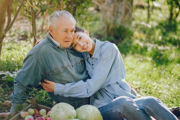 Oude oudste die zich in een de zomertuin bevindt met oogst