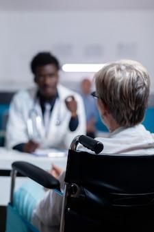 Oude patiënt met een handicap krijgt consultatie van zwarte dokter