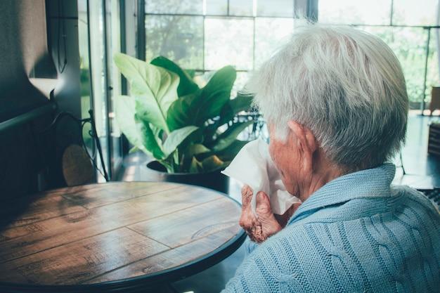Oude persoon die behandelend mond met een weefsel op een huisbinnenland hoesten. ze heeft griep, allergiesymptomen, acute bronchitis, longinfecties of longontsteking.
