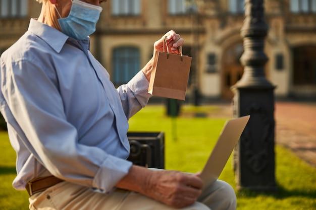 Oude persoon die laptop vasthoudt terwijl hij in de tuin zit