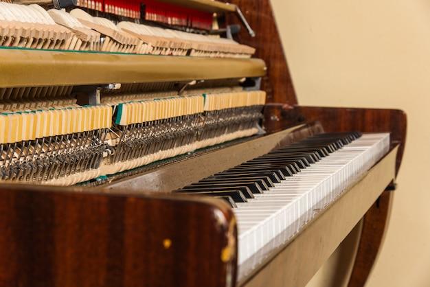 Oude piano geïsoleerd op de muur