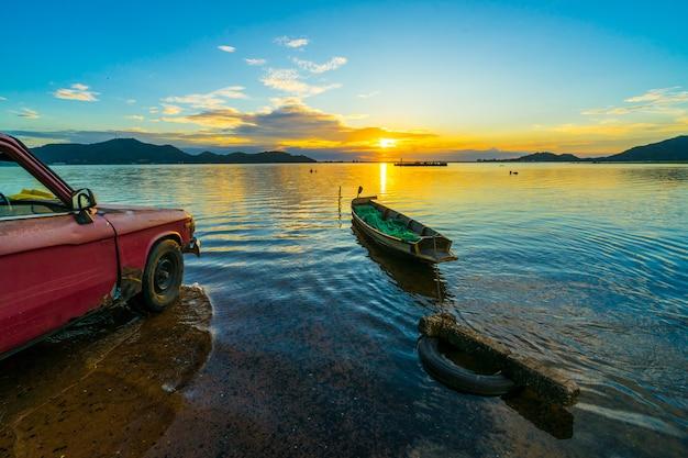Oude pick-up die op de waterkant met zonsondergang bij het reservoir van klappra wordt geparkeerd, sriracha chon buri, thailand