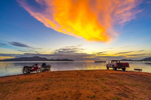 Oude pick-up en motorfiets die aan de waterkant met zonsondergang bij het reservoir van klappra wordt geparkeerd
