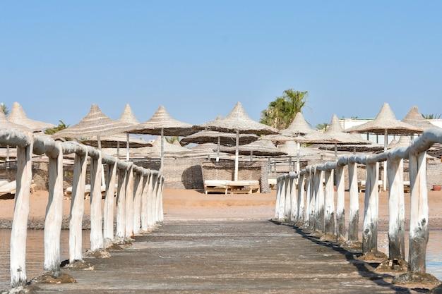 Oude pier met een houten hek aan de kust van de zee strand