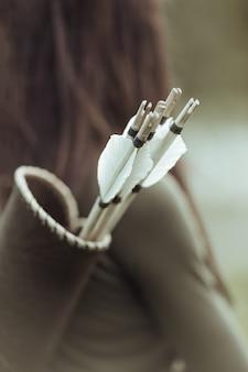 Oude pijlkoker met pijlen op de rug van een vrouwelijke boogschutter, close-up