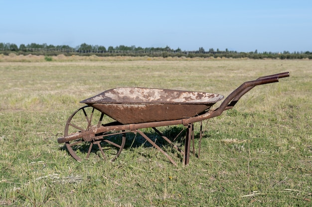Oude plaatwerk kruiwagen in veld