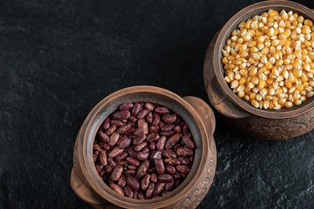 Oude pot met ongekookte bruine bonen en popcorn