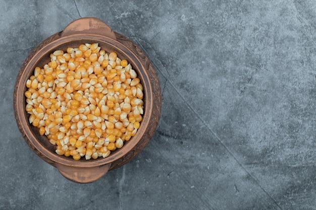 Oude pot vol rauwe popcorn op een grijs