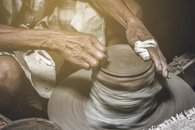 Oude pottenbakker die kom op de achtergrond van het aardewerkwerk maakt.