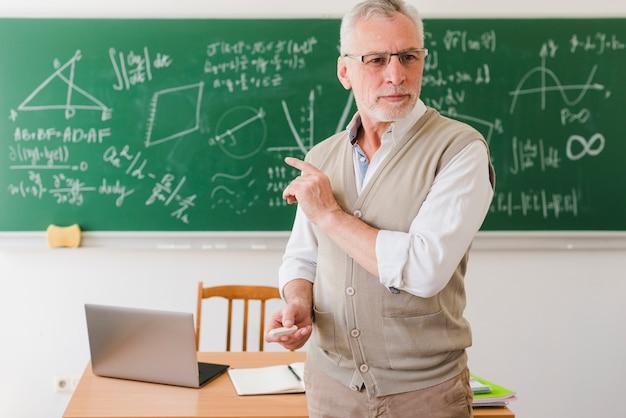 Oude professor die in klaslokaal toont