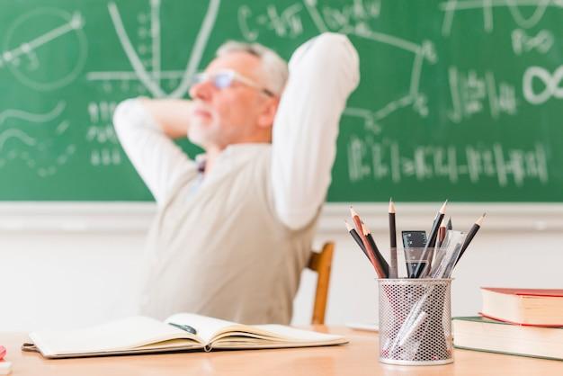 Oude professor die in lezingsruimte rust