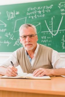 Oude professor schrijven in collegezaal