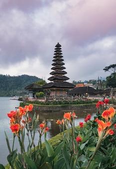 Oude pura ulun danu bratan-tempel met oranje bloem die in bali bloeien