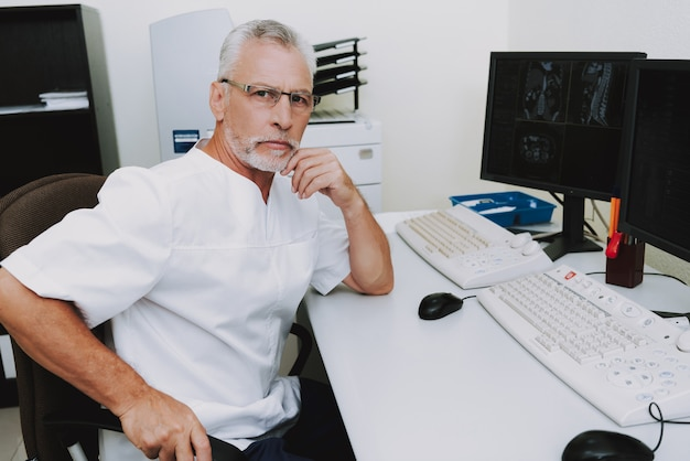 Oude radiologieprofessor onderzoekt röntgenscans.