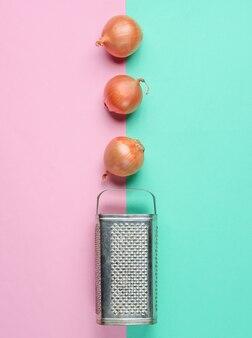Oude rasp en ui bollen op pastel oppervlak.