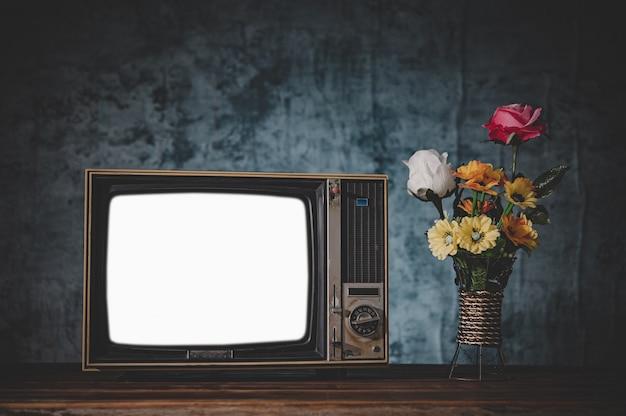 Oude retro-tv het is nog steeds leven met bloemenvazen