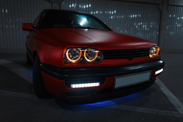 Oude rode auto met nieuwe optica op de parkeerplaats 's nachts