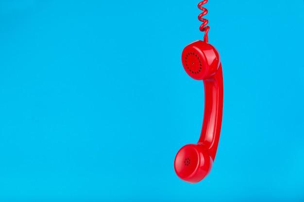 Oude rode telefoonhoorn opknoping op een blauwe ondergrond
