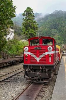 Oude rode trein in alishan line (bergaf) komt op mistige dag terug naar chiyi treinstation.
