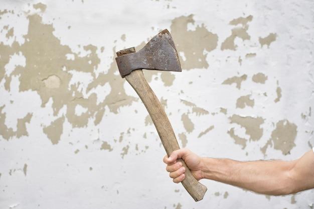 Oude roestige bijl in de hand van de man tegen de armoedige muur