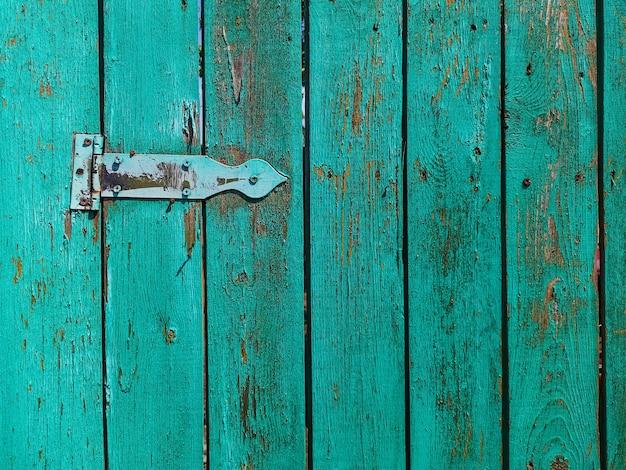 Oude roestige deurscharnier op een houten omheiningsdeur
