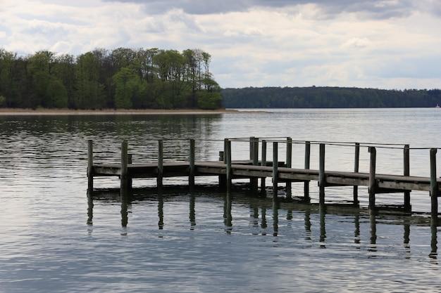 Oude roestige dok aan het meer omgeven door prachtige bomen in middelfart, denemarken
