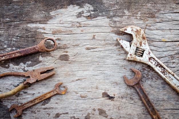 Oude roestige hulpmiddelen op oude houten achtergrond. moersleutel op houten. rustieke stijlen. bovenaanzicht