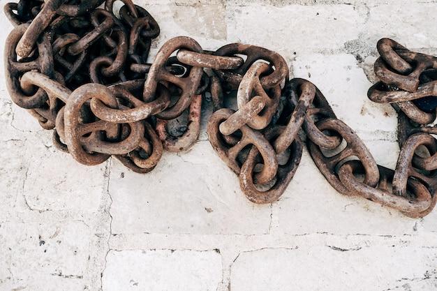 Oude roestige ketting op een stenen oppervlak verschillende schakels van een roestige oude ketting