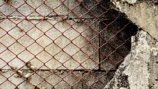 Oude roestige kooi bij de schade concrete muur.