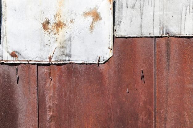 Oude roestige metalen platen die werden gebruikt om de schuurmuur te bouwen, een deel was verwend en vervangen door nieuwe zonder roest, een close-up van de reparatie