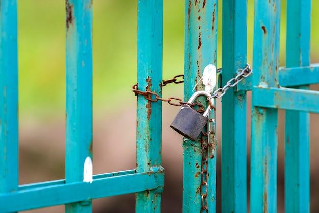 Oude roestige poort met geketend hangslot.