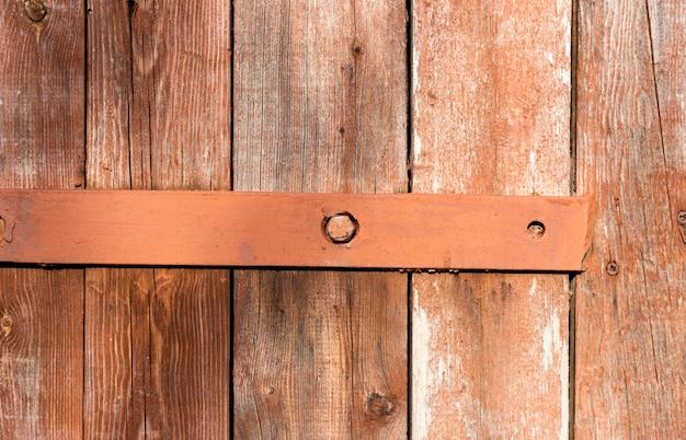 Oude roestige scharnier op houten deur, oude achtergrond