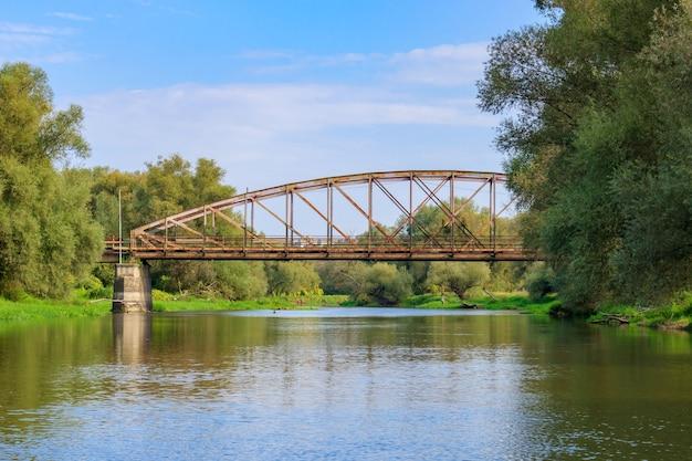 Oude roestige spoorbrug over de rivier op een blauwe hemelachtergrond. rivierlandschap op zonnige herfstochtend