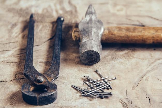 Oude roestige tangen, spijkers en hamer op een houten ondergrond.