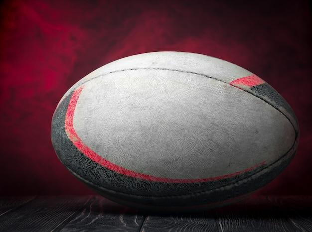 Oude rugbybal op een rode muur