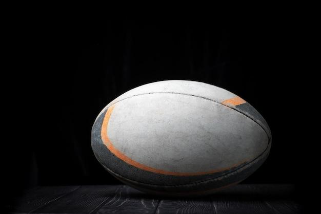 Oude rugbybal op een zwarte muur