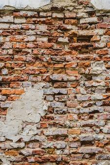 Oude ruïnesbakstenen muur met gebarsten beton