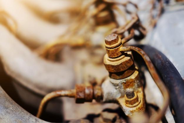Oude rustieke knoop en roestige ijzerkettingen die met zonlicht op motor van auto worden geknoopt