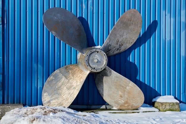 Oude scheepsschroef verslechtert in de winter op de scheepswerf. roestige scheepspropeller op blauwe muurachtergrond.