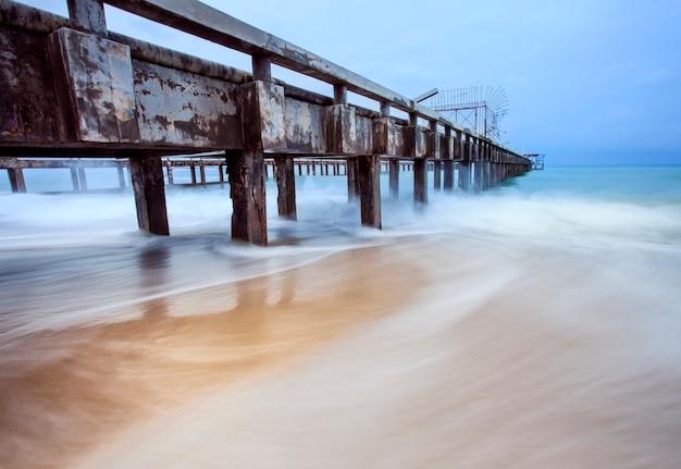 Oude schip pier en zee golven in stormseizoen