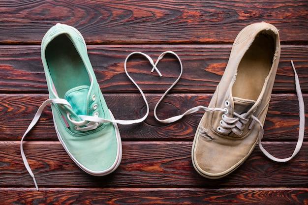 Oude schoenen en hart van kant op de houten achtergrond