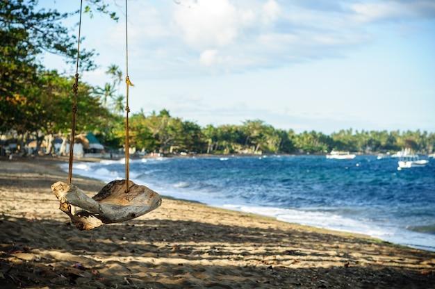 Oude schommel op het strand in de buurt van de zee in dumaguete, filippijnen