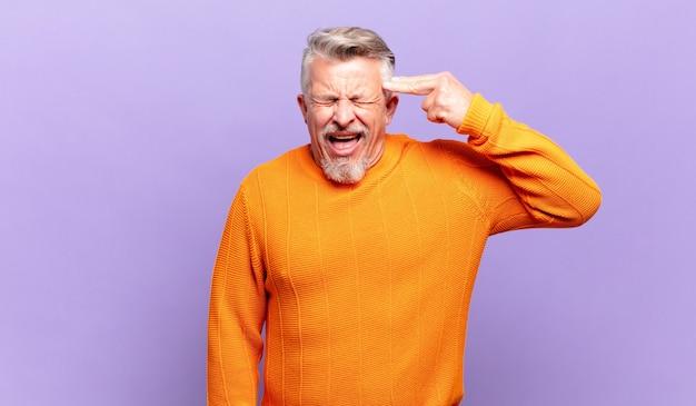 Oude senior man die er ongelukkig en gestrest uitziet, zelfmoordgebaar maakt een pistoolteken met de hand, wijzend naar het hoofd