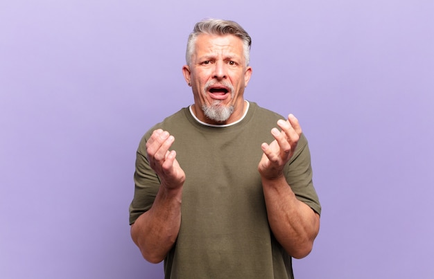 Oude senior man die er wanhopig en gefrustreerd uitziet, gestrest, ongelukkig en geïrriteerd, schreeuwend en schreeuwend