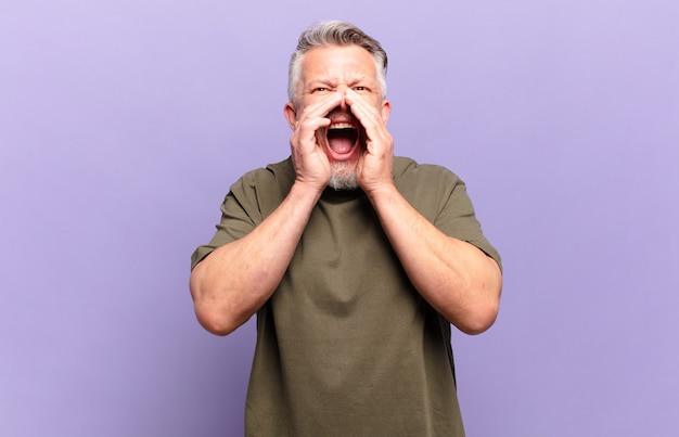 Oude senior man die zich gelukkig, opgewonden en positief voelt, een grote schreeuw geeft met de handen naast de mond, roept