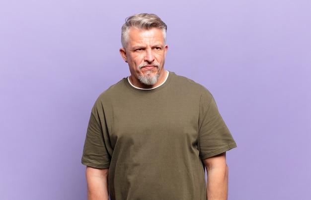 Oude senior man die zich verdrietig, overstuur of boos voelt en opzij kijkt met een negatieve houding, fronsend in onenigheid