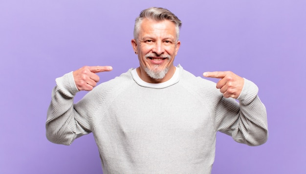 Oude senior man glimlachend vol vertrouwen wijzend naar eigen brede glimlach, positieve, ontspannen, tevreden houding