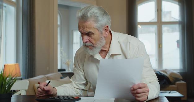 Oude senior man huis financiën en rekeningen controleren, is hij kosten berekenen, met behulp van computer en het schrijven van notities.