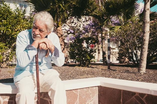Oude senior man met handen over het riet zitten in openbaar park met droevige uitdrukking. oudere gepensioneerde met rugpijn met behulp van wandelstok. boom en bloemen op achtergrond
