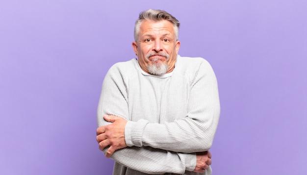 Oude senior man schouderophalend, verward en onzeker, twijfelend met gekruiste armen en verbaasde blik